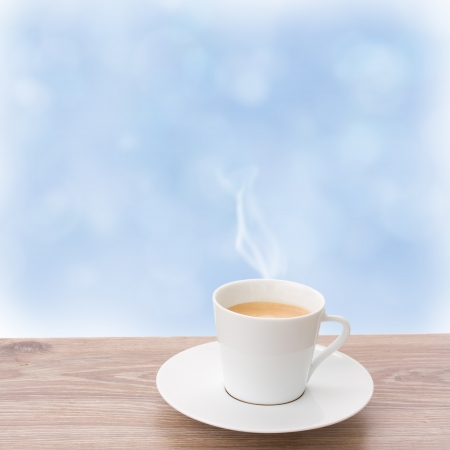 cup of coffee on wooden sill and  blue sky background photo