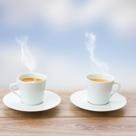 two cup of coffee on wooden table and  blue sky background photo