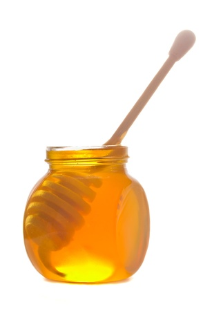 glass pot  with honey and stick isolated on white background Stock Photo - 18591531
