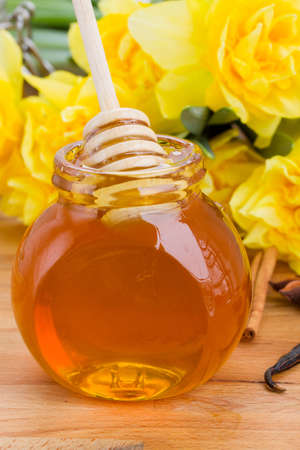 glass jar of polyfloral honey   on wooden table photo