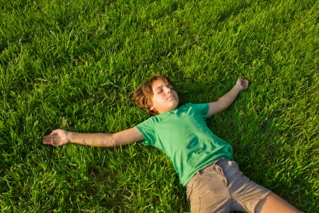 summer leisure - boy relaxing on green grass