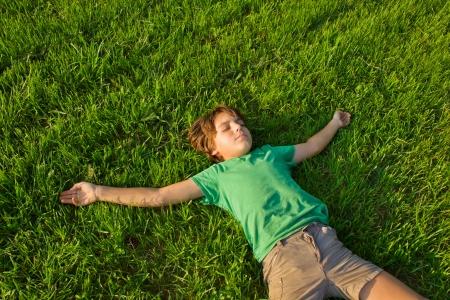 wypoczynek letni - Chłopiec relaks na zielonej trawie