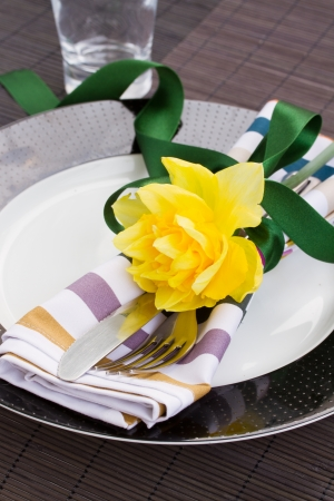 table serving   -  knife and fork with nacissus flower on a plate