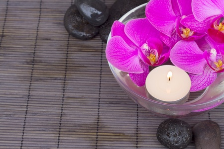 bowl with orchids and candle and massage black  stones photo