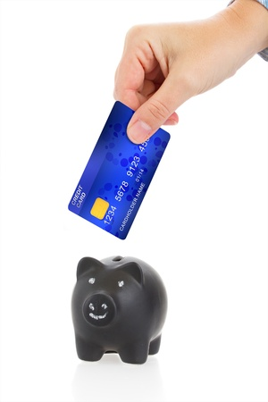 human hand insert credit card in to piggy bank isolated on white background photo