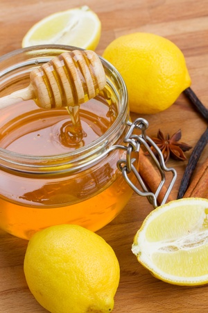 glass honey pot, spices and lemons on wooden table photo