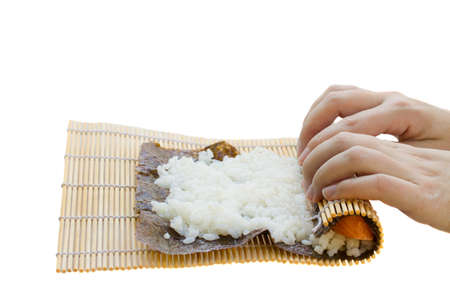 sushi preparation - rolling bamboo mat for  sushi maki roll photo
