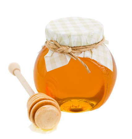 glass pot  with floral honey and stick isolated on white background photo