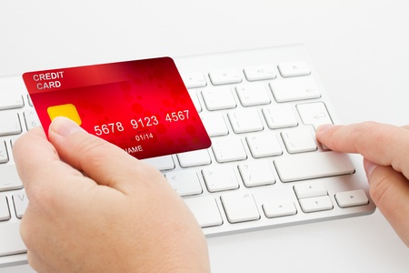 technology transaction: hands holding plastic card  and press enter on white keyboard Stock Photo