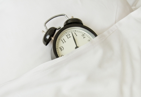 snoozing: alarm clock sleeping in white linen bed