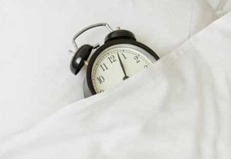 white linen: reloj despertador para dormir en la cama de lino blanco