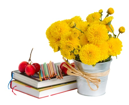 Books and yellow mums flowers on white back to school concept photo