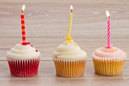 birthday cupcakes with burning candles on wooden table photo