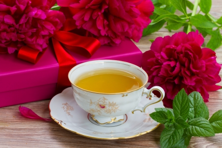 mint  cup of tea with red peonies and gift box photo