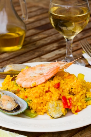 Dining  -  plate with paella and glass of wine photo
