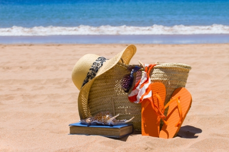sunbathing accessories on sandy beach by the ocean photo