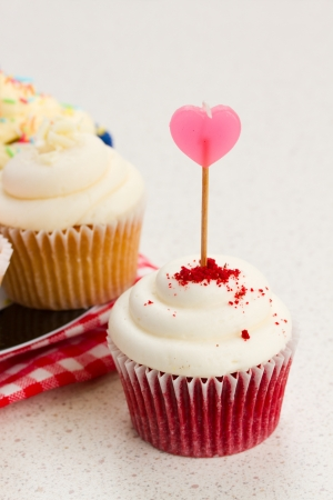 berry cupcake with pink heart stick close up photo