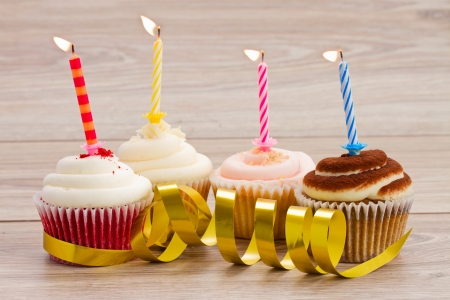 four birthday cupcakes with burning candles on wooden table Imagens