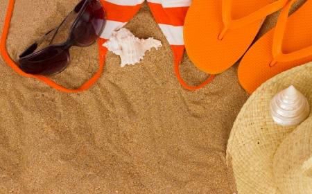 orange sandals  and sunbathing accessories at sand with copy space photo