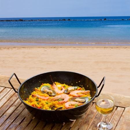 Paella de marisco con un vaso de vino en la cafetería junto al mar