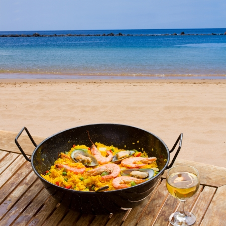 tapas espa�olas: Paella de marisco con un vaso de vino en la cafeter�a junto al mar
