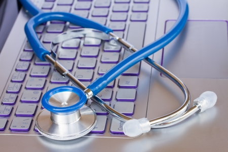 stethoscope on laptop keyboard - modern medicine concept photo