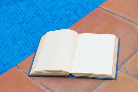 summer reading open book at pool side photo