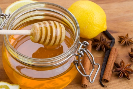 honey stick and honey pot and lemons on wooden table photo