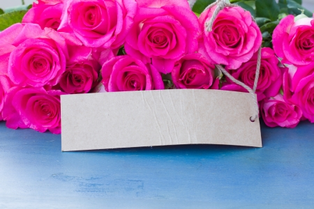 pink roses on wooden table with paper tag photo