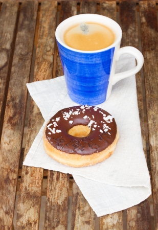 donut with coffee mug served on wooden table photo