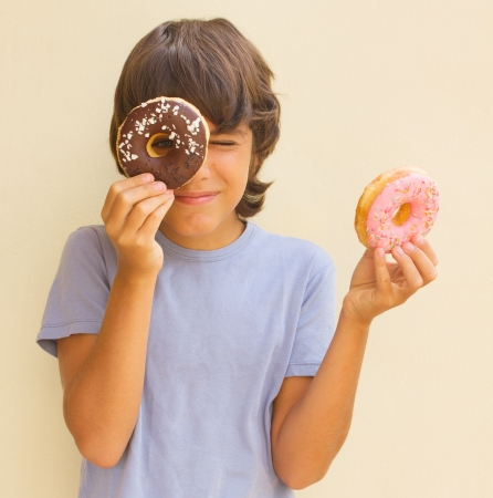teen  caicasian boy playing with  donuts photo