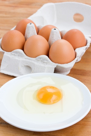 raw eggs for cooking one in plate and six in box on wooden table photo