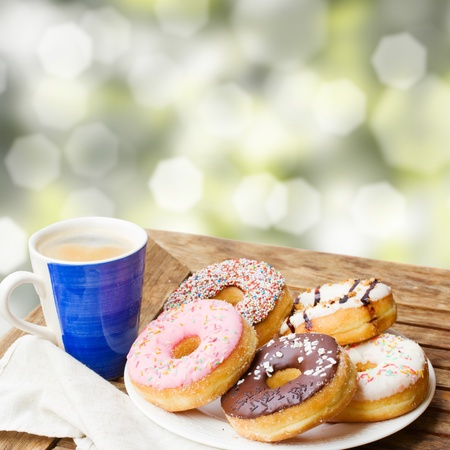 coffee mug and plate of donuts served on wooden table in garden photo