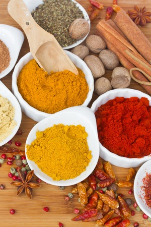colorful spices of curry, cucrma and red pepper with seeds of anise and nutmeg on wooden table photo