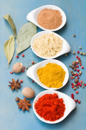colorful spices of  cucrma, red pepper, ginger and nutmeg with seeds of anise  on  blue wooden table photo