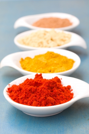 colorful spices of cucrma, red pepper, ginger and nutmeg on blue table photo