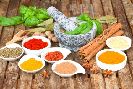 colorful mix of plates spices and mortar on wooden table photo