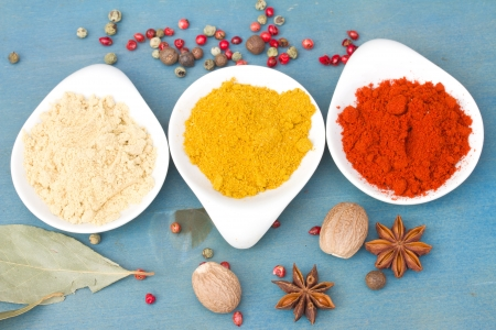 colorful mix of spices of  cucrma, red pepper and  ginger with seeds of anise  on  blue wooden table photo