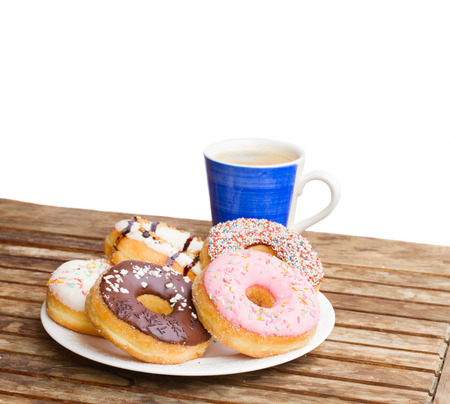 plate of donuts  and blue coffee mug served on wooden table in garden photo