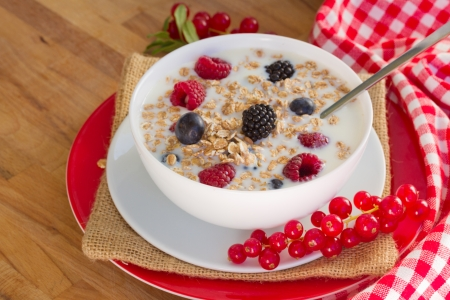 The oat flakes with berries on wooden table Stock Photo