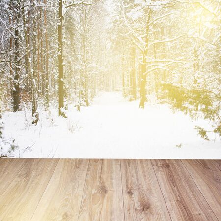 wooden planks with snowed winter forest background photo