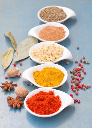 colorful spices of  cucrma, red pepper, ginger, nutmeg  and basil with seeds of anise  on  blue wooden table photo