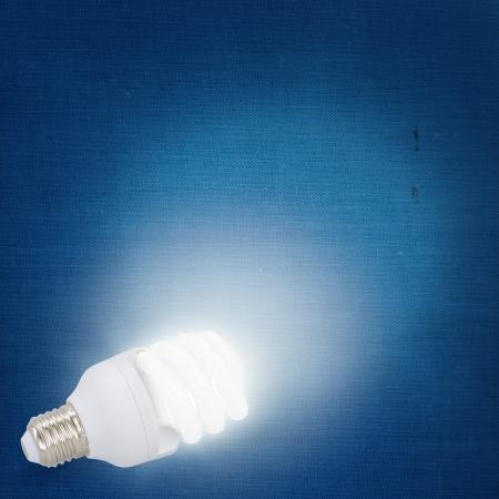Illuminated modern light bulb on blue background photo