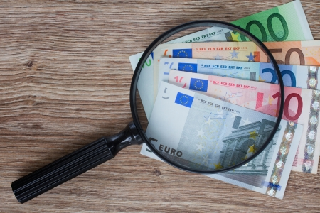 dinero falso: pila de billetes en euros bajo la lupa