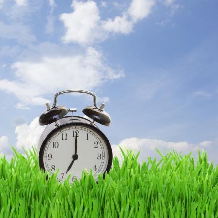 concepto de tiempo - reloj de alarma en la hierba en el cielo azul Foto de archivo