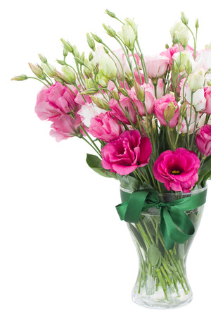 Pink eustoma flowers in glass vase isolated on white photo