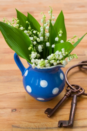 Lilly of the valley bouquet in blue pot on wooden table photo