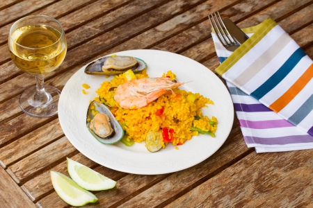 marisco: Paella, traditional spanish dish  served in plate on wooden table