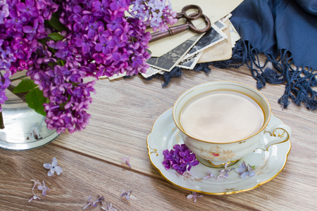 summer tea time - cup of tea with lilac  and vintage photos photo