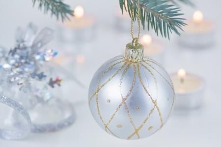 felicitaciones navide�as: plata bola de Navidad colgando de abeto y luz de las velas desenfocado